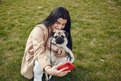 Woman in Brown Coat Holding Her Dog While Taking Selfie