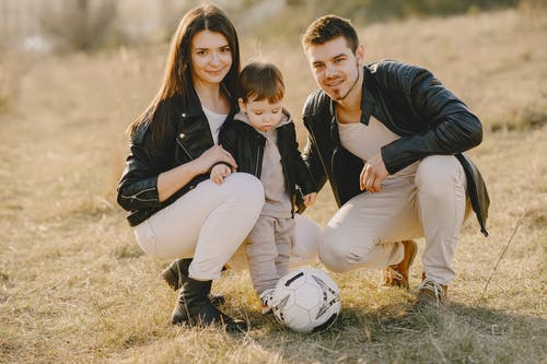 Photo of Family Wearing Black Leather Jacket While Sitting on Grass Field