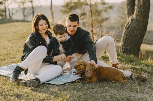 Photo of Family Sitting on Mat While Looking at Brown Dog