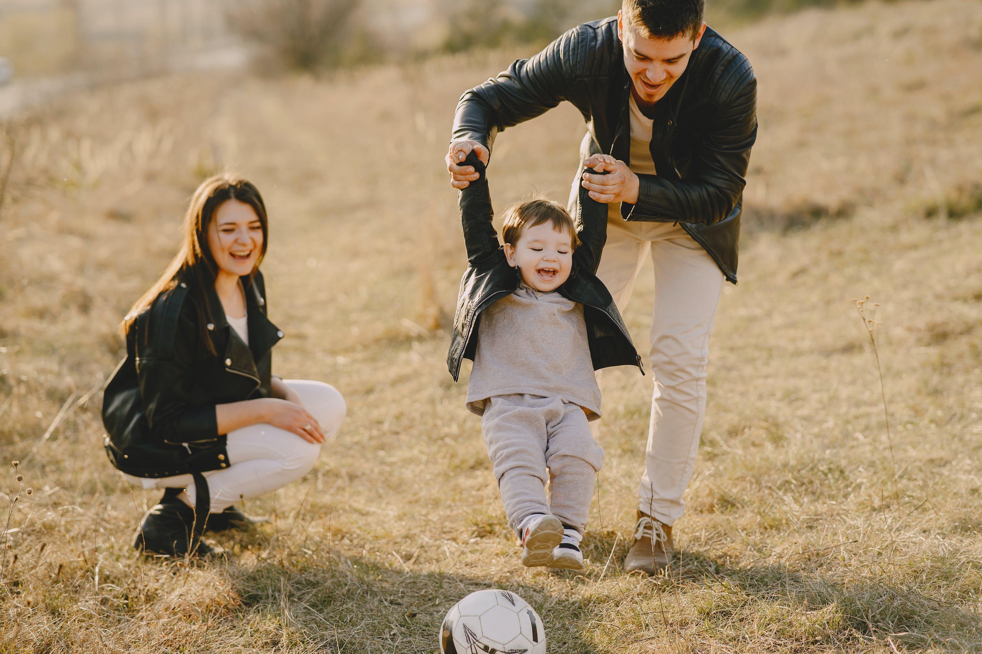Фотография семьи, развлекающейся с футбольным мячом