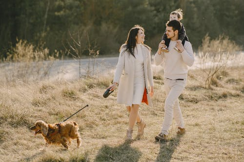 Photo of Family Walking on Grass Field With Their Dog
