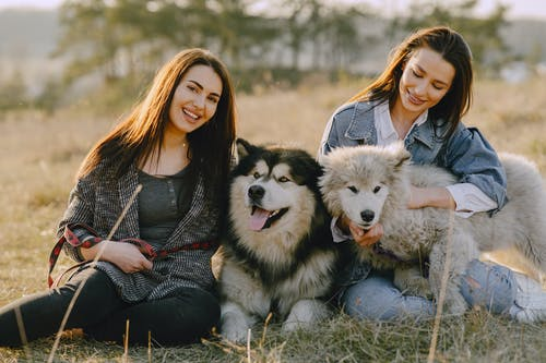 Photo of Women Holding Their Dogs While Sitting on Grass
