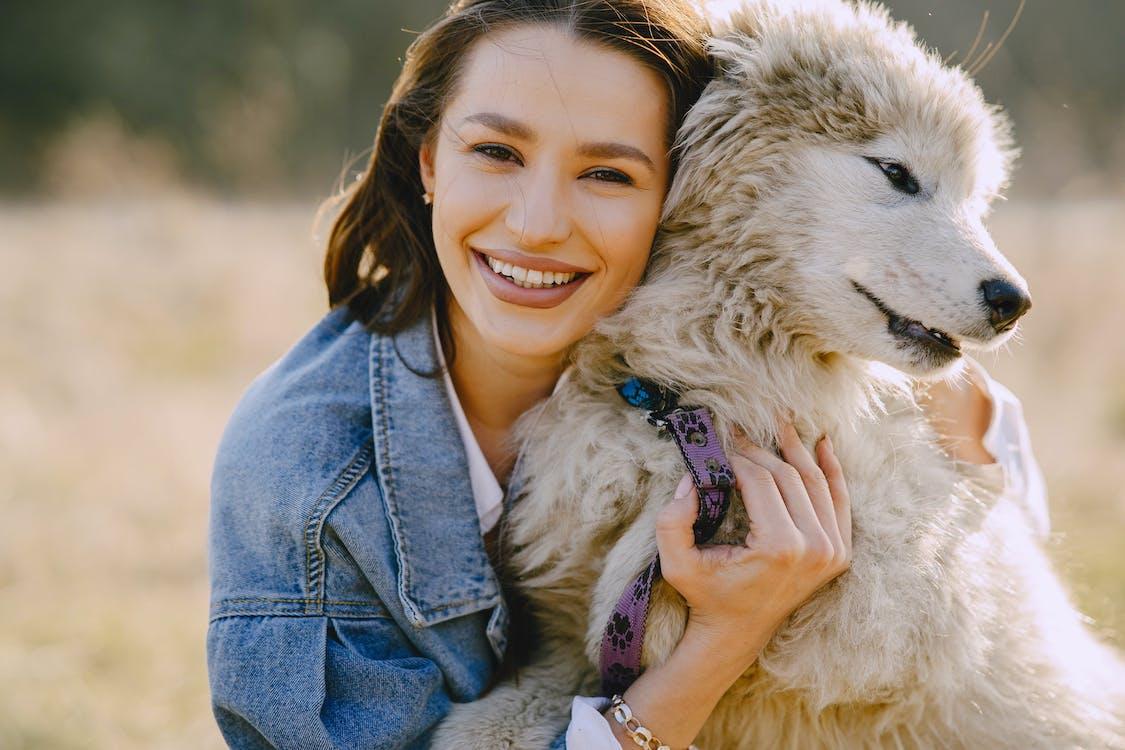 Woman in Blue Denim Jacket Holding White Dog