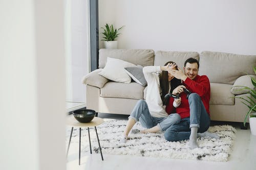 Man and Woman Sitting Carpet While Smiling