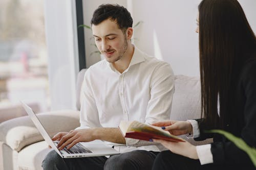 Smiling male coworker with laptop and female colleague with book