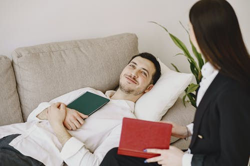 Cheerful man talking with therapist and lying on sofa