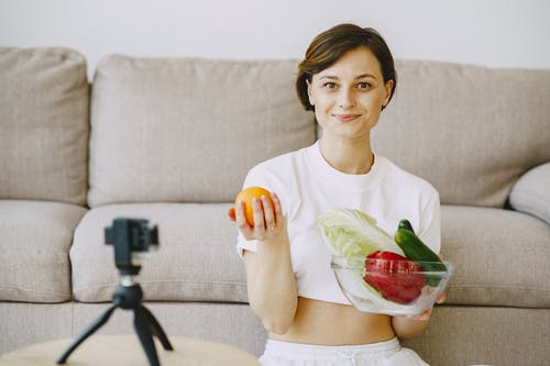 Optimistic female in white clothes sitting near sofa and holding bowl with fresh vegetables and orange in hands and looking at camera
