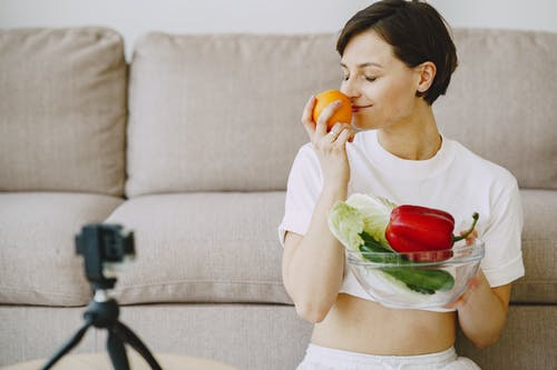 Photo of Woman Holding Orange Fruit and Bowl With Vegetables