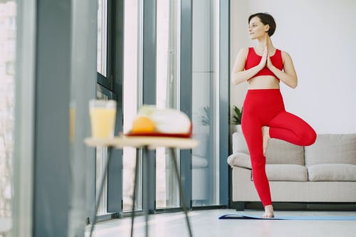 Slim woman doing yoga exercise in living room