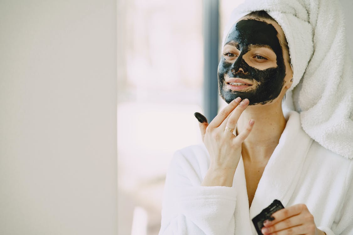 Photo of Woman Applying Clay Mask on Her Face
