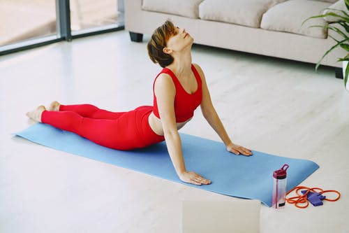 Flexible woman doing yoga stretch on fitness mat