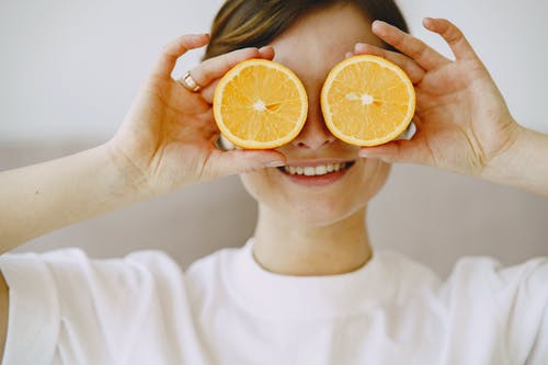 Unrecognizable woman with slices of orange
