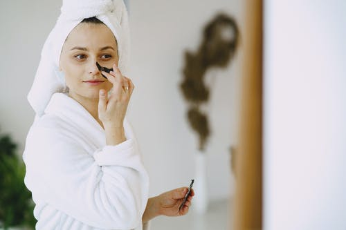 Content woman applying facial mask on face