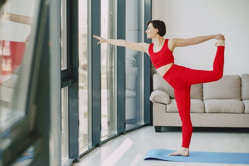 Cheerful woman stretching body on yoga mat