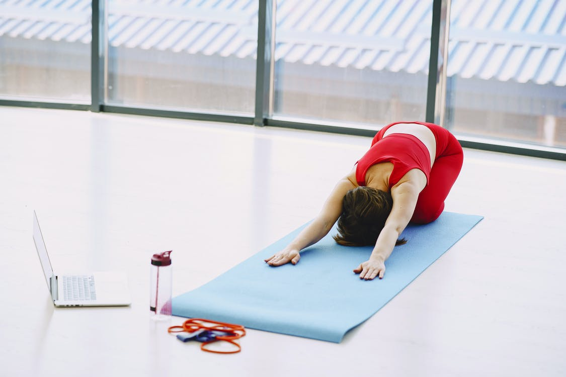 Young woman performing yoga exercise and using laptop at home