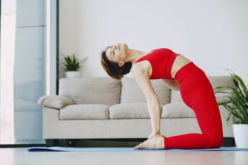 Woman in Red Tank Top and Red Leggings Lying on Blue Yoga Mat