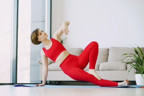 Young woman performing yoga exercise at home