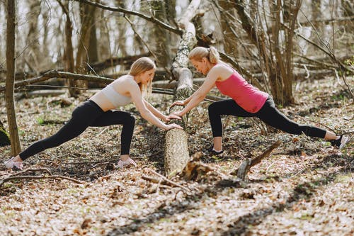 Flexible sportswomen doing stretching exercise in nature