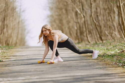 Photo of Woman Exercising With Dumbbells on a Pavement