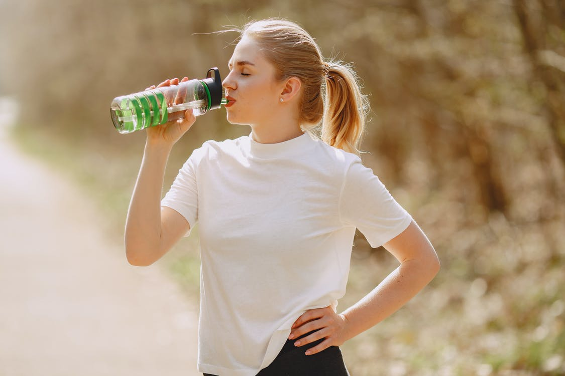 Woman in White Crew Neck T-shirt Drinking from Green Plastic Bottle