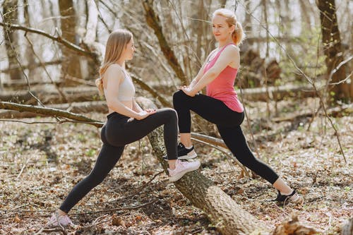 Flexible sportswomen doing stretching exercise in forest