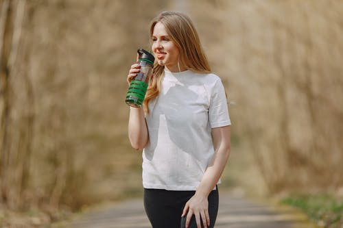 Smiling woman drinking water during training in park