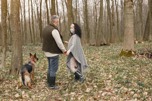 Man and Woman Walking With Dog on Forest