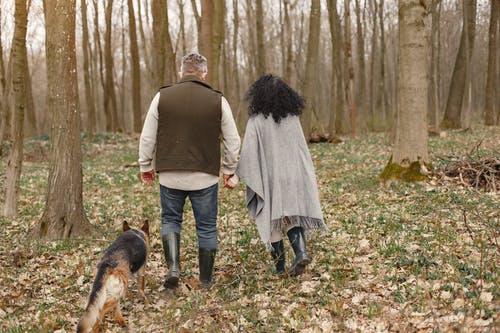 Man and Woman Walking on Forest With Their Dog