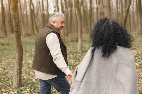 Photo of Man and Woman Holding Hands While Walking at Forest
