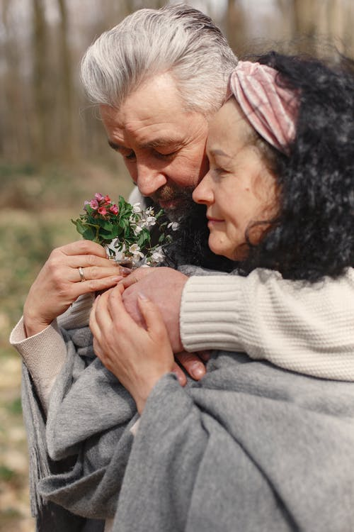 Man in Gray Sweater Hugging Woman in White Sweater Holding White Flowers