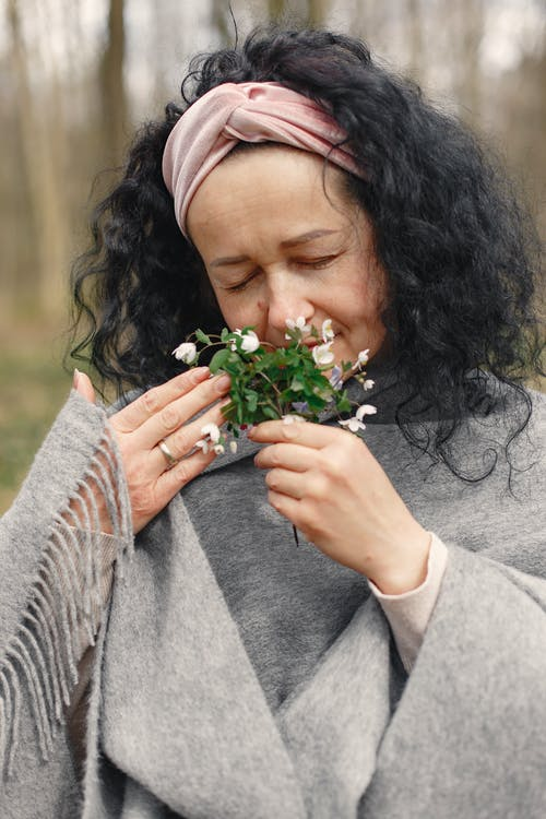Woman in Gray Scarf While Smelling White Flowers
