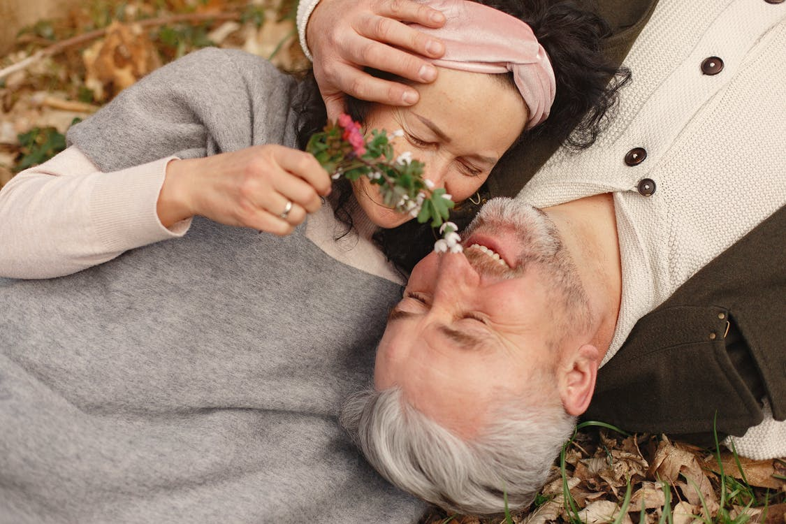 From above of cheerful senior wife wearing wide scarf and headband with flower bouquet in hand and happy elderly gray haired husband in warm clothes lying on ground with fallen leaves in park with closed eyes