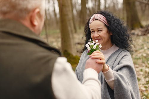 Happy senior couple in love with flowers in forest