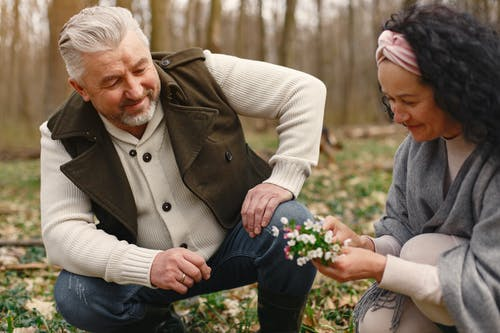 Happy elderly couple in love with fresh flowers in forest