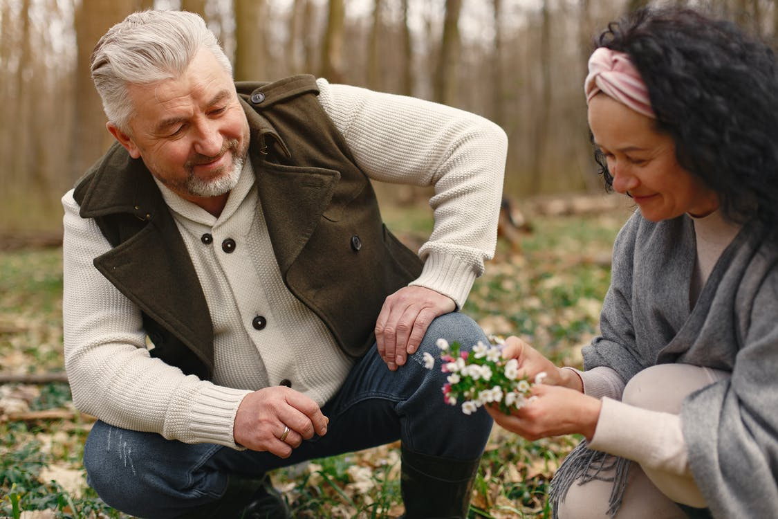 Happy senior wife wearing wide scarf and headband smiling while sitting on ground in autumnal forest with delicate flowers in hands near cheerful elderly gray haired husband in warm clothes while strolling together