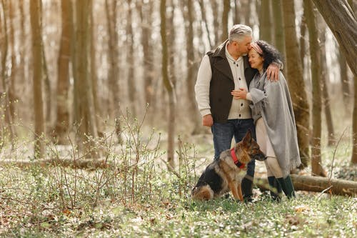 Elderly couple walking with dog in forest