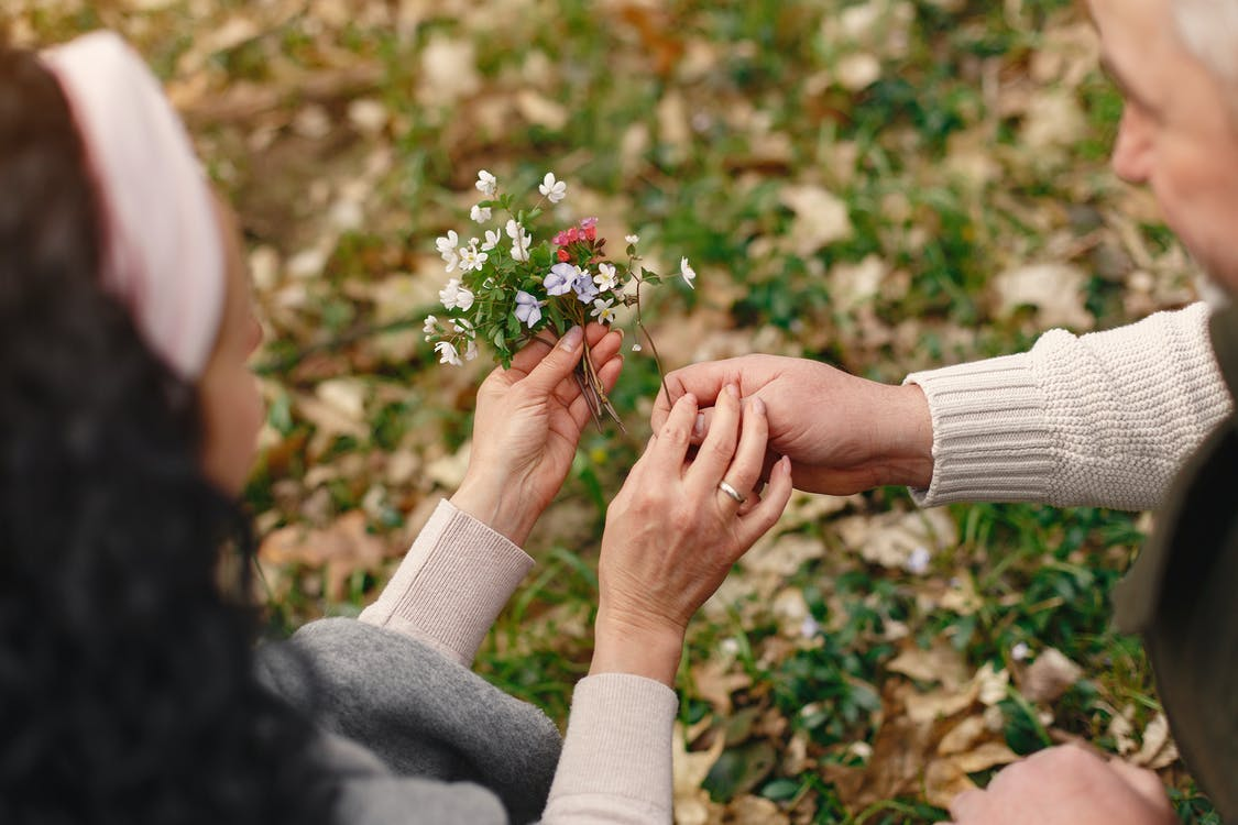 Crop senior couple holding flowers in park
