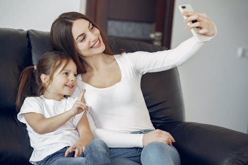 Smiling mother and daughter taking selfie on smartphone at home