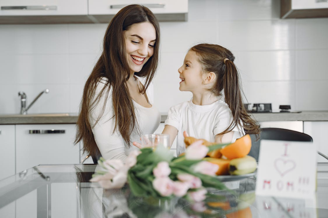Happy mother and daughter enjoying morning meal in kitchen