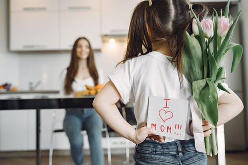 Daughter preparing surprise for mother at home
