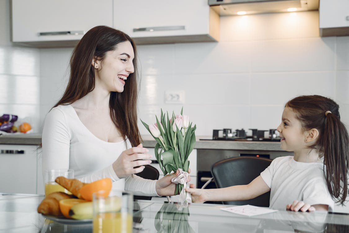 Happy girl presenting flowers to mother on kitchen