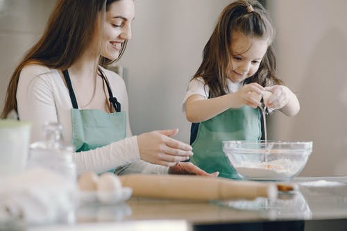Photo of Mom and Child Baking With Egg and Flour