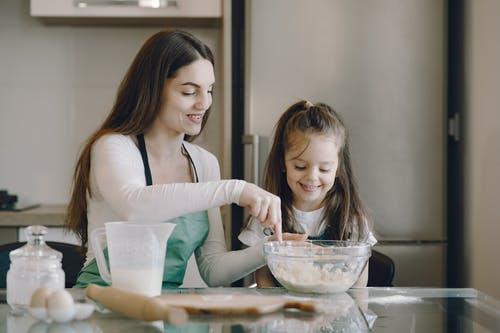 Photo of Woman and Child Smiling While Baking