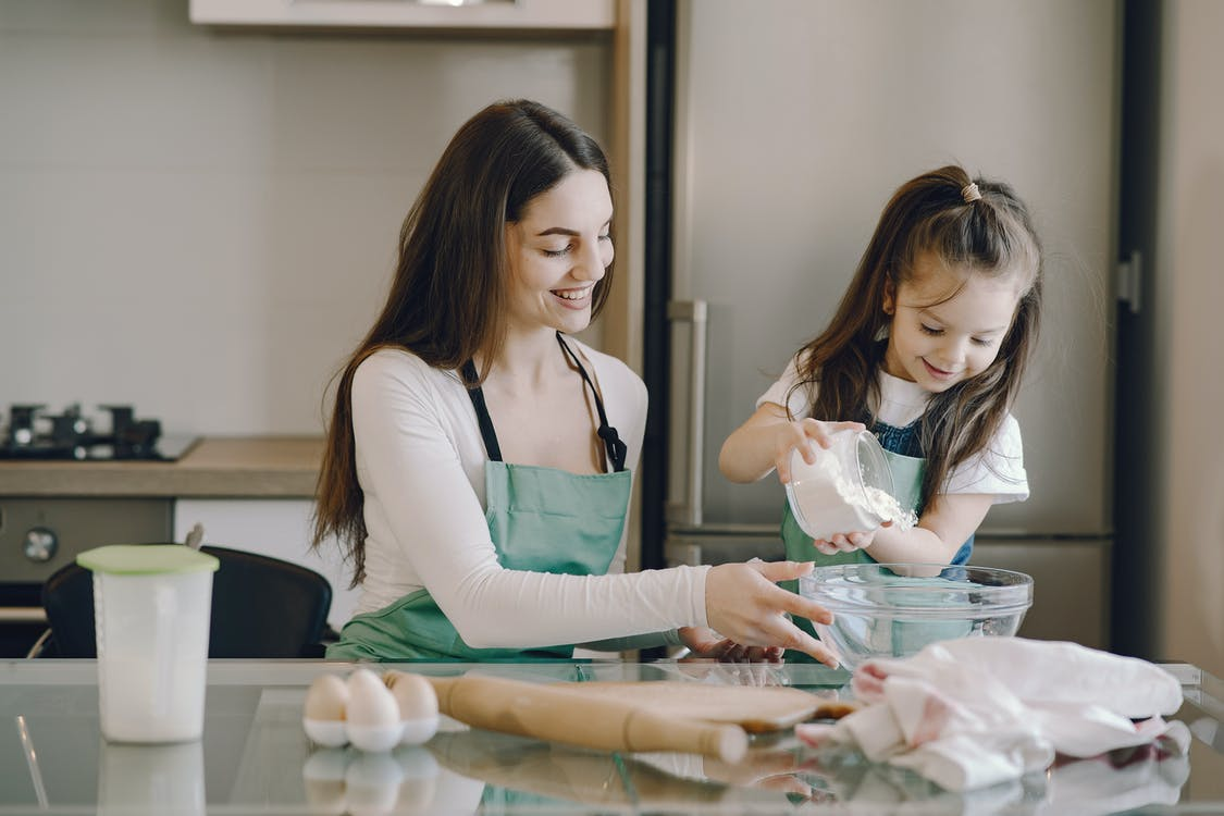 Photo of Girl Pouring Flour on Bowl