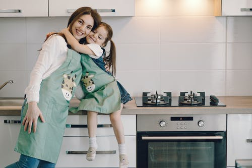 Photo of Girl Hugging Her Mom While Sitting on Kitchen Counter