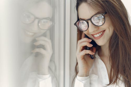 Happy young woman speaking on smartphone near window