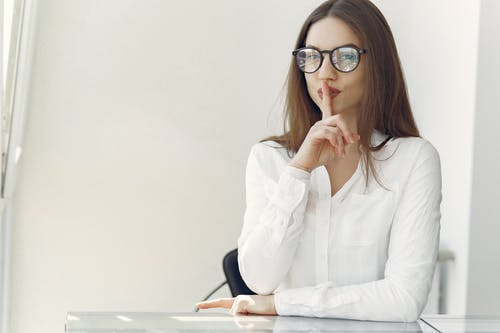 Flirty young lady asking to keep secret sitting in office