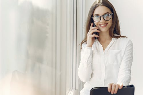 Cheerful young female secretary using on smartphone at workplace