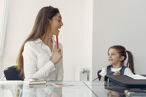 Cheerful woman and kid having fun in office