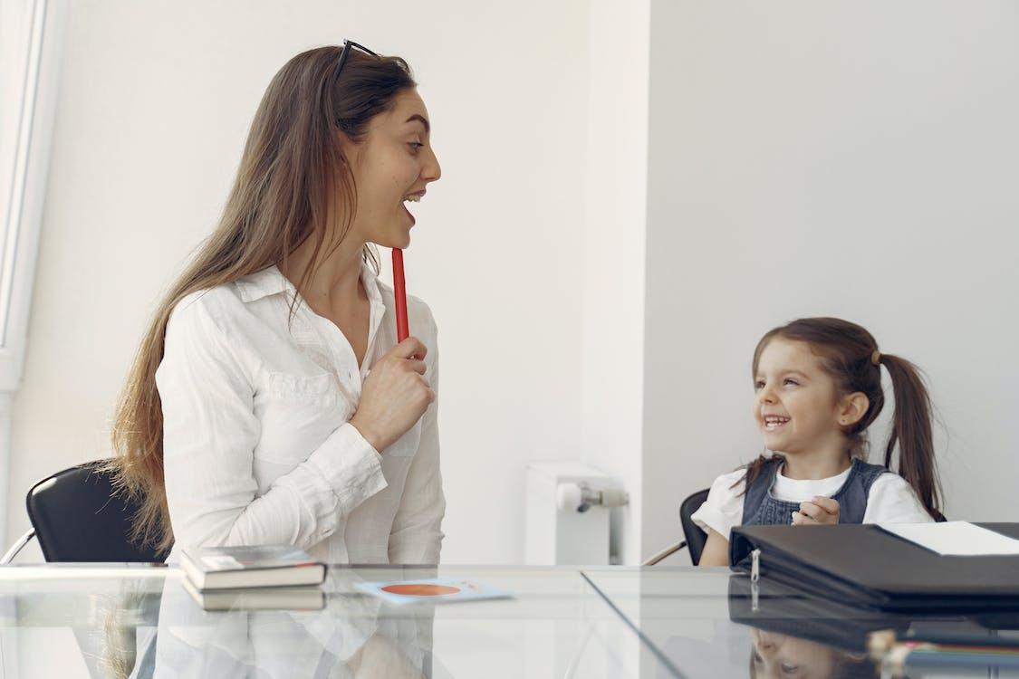 Cheerful woman and kid having fun in office